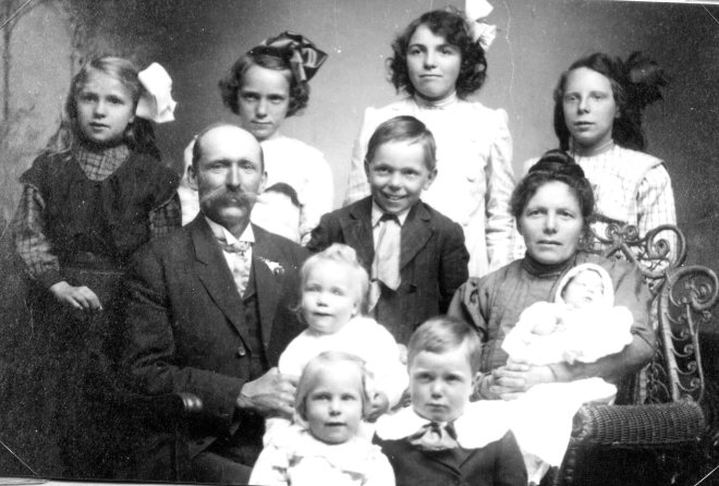 Back row: Bertha, Anna, Clara, Louise. Seated row: Charles, Charles, Christina. Lap children: Preston, Laura. Front: Ida, Joseph.