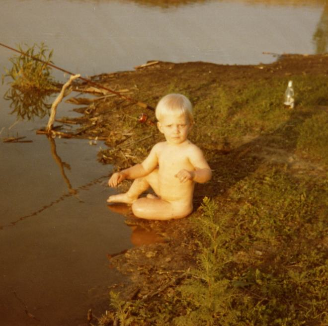 Naked Paul Ross sitting in lake at camera